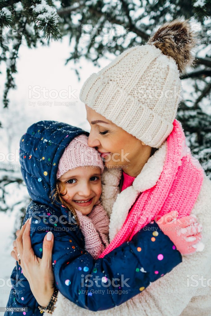 Mother and daughter kissing and hugging in snow stock photo