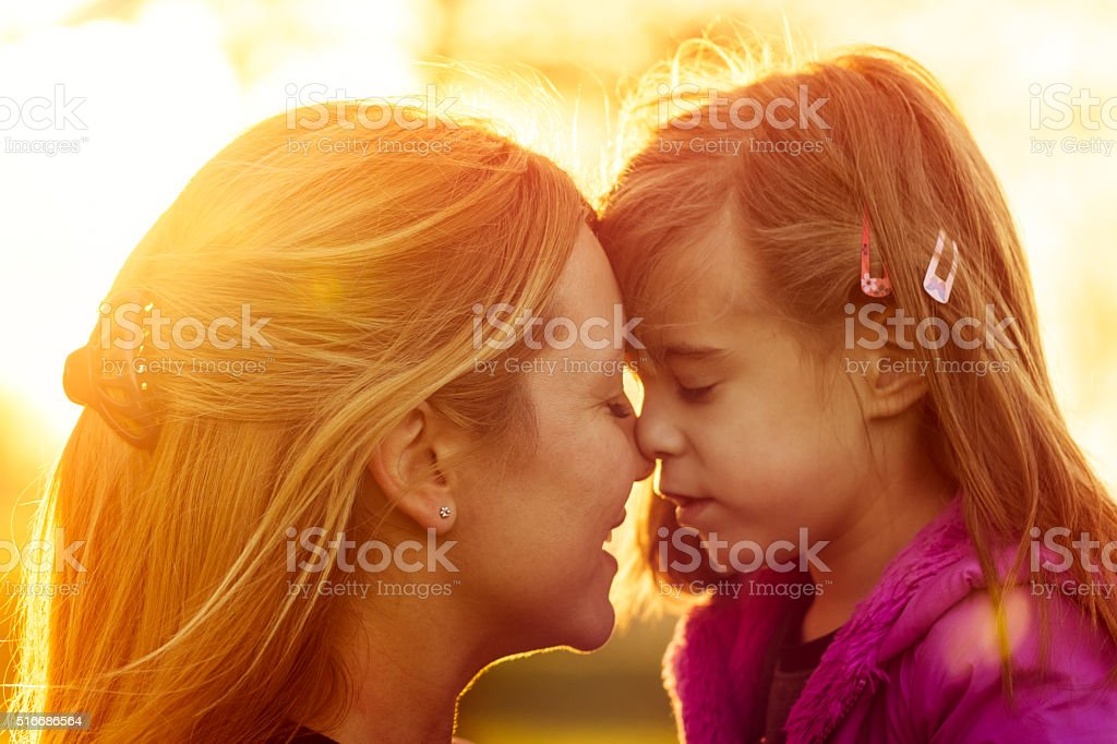 Mother and daughter kissing at sunset closeup stock photo