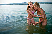 Mother and daughter laughing in lake