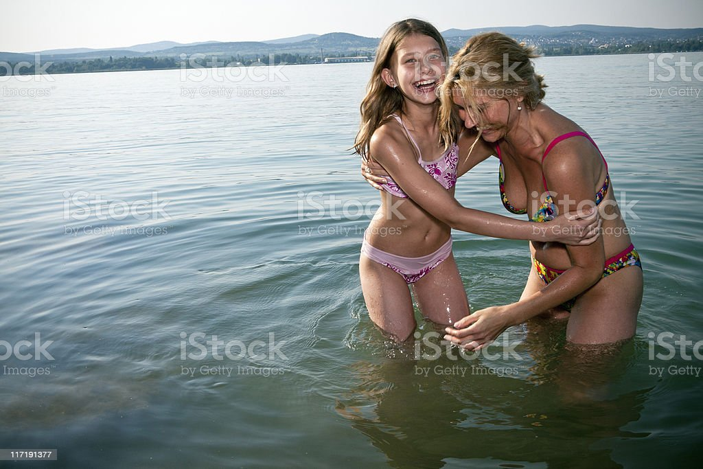 Mother and daughter laughing in lake stock photo