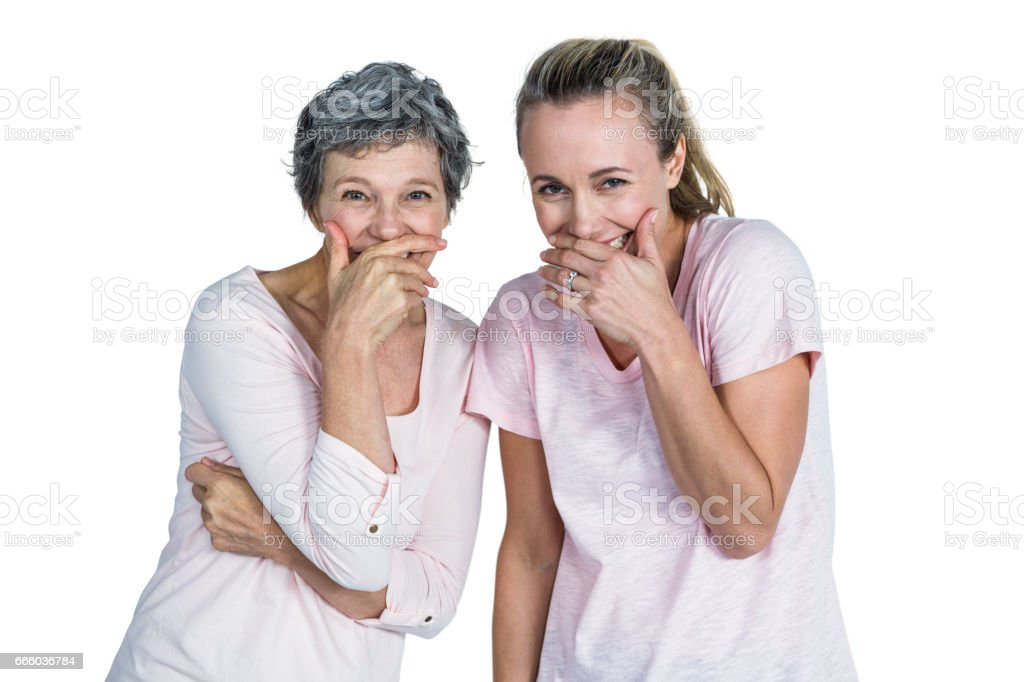 Mother and daughter laughing with hand on mouth stock photo