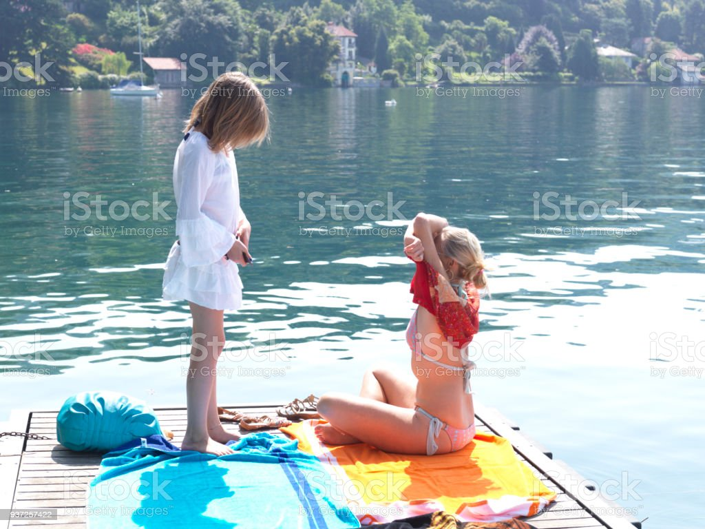 Mother and daughter lay out towels on dock on lake Lake, forest and houses behind 14-15 Years Stock Photo