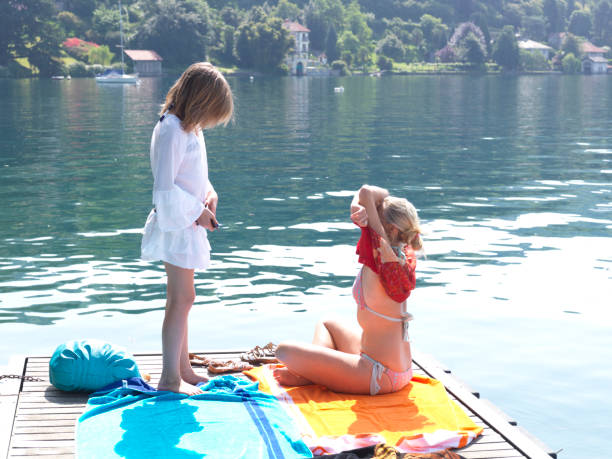 Mother and daughter lay out towels on dock on lake Lake, forest and houses behind middle aged women in bikinis stock pictures, royalty-free photos & images