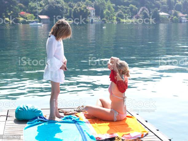 Mother And Daughter Lay Out Towels On Dock On Lake Stock Photo - Download Image Now