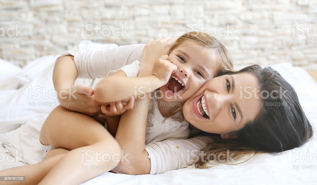 Mother and daughter laying in bed. stock photo