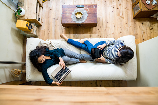 istock Mother and daughter laying on the sofa using smart devices 627916820