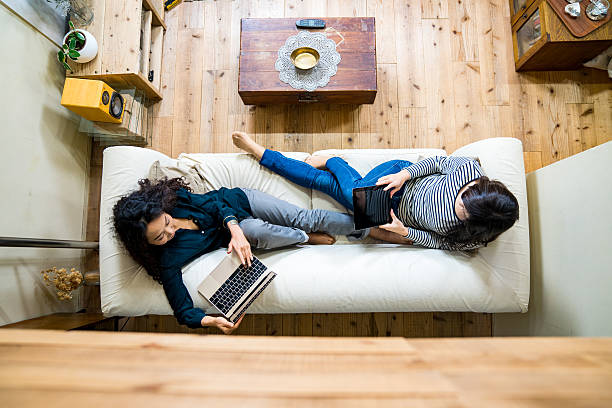 Mother and daughter laying on the sofa using smart devices stock photo