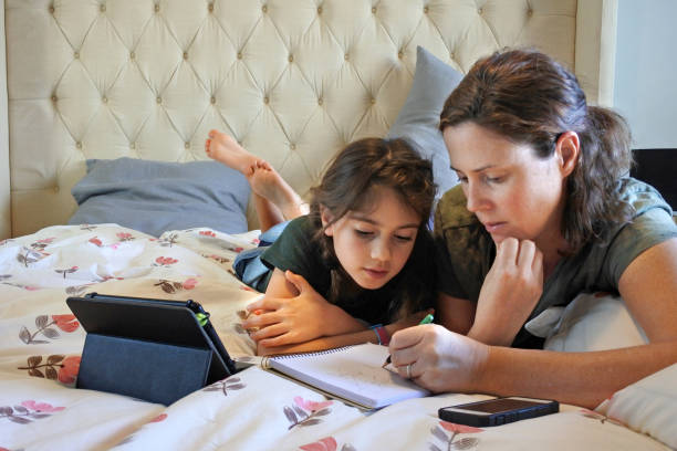 Mother and daughter learning together in bedroom while forced to stay at home because government policies efforts to prevent pandemic coronavirus (COVID-19) spreading stock photo