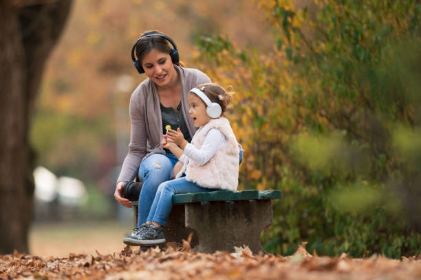 Mother and daughter listening to music stock photo