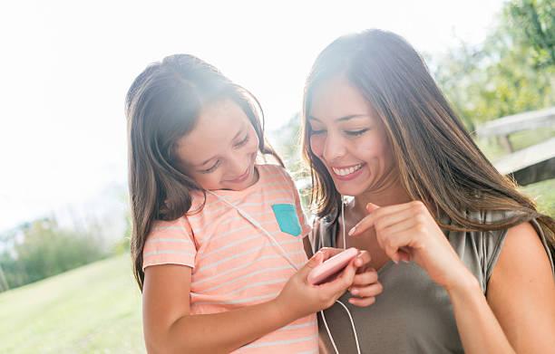 madre e hija escuchar música - mp4 fotografías e imágenes de stock