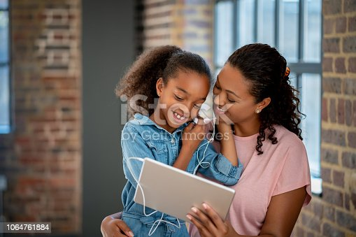 Portrait of a happy mother and daughter listening to music with earphones on a digital tablet and smiling - lifestyle concepts
