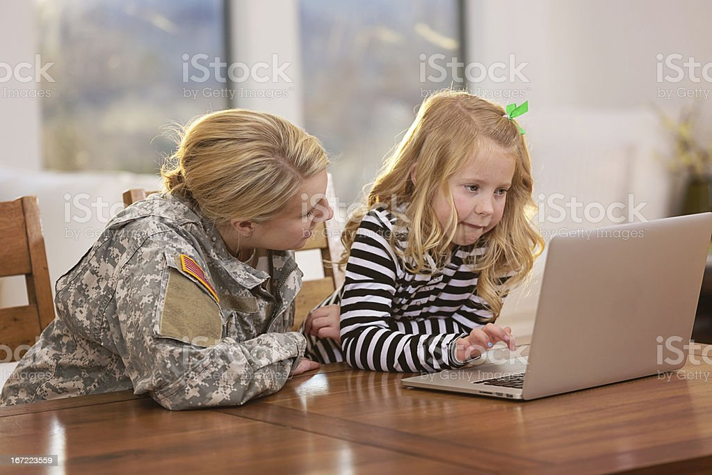 Mother and daughter looking at a laptop together royalty-free stock photo