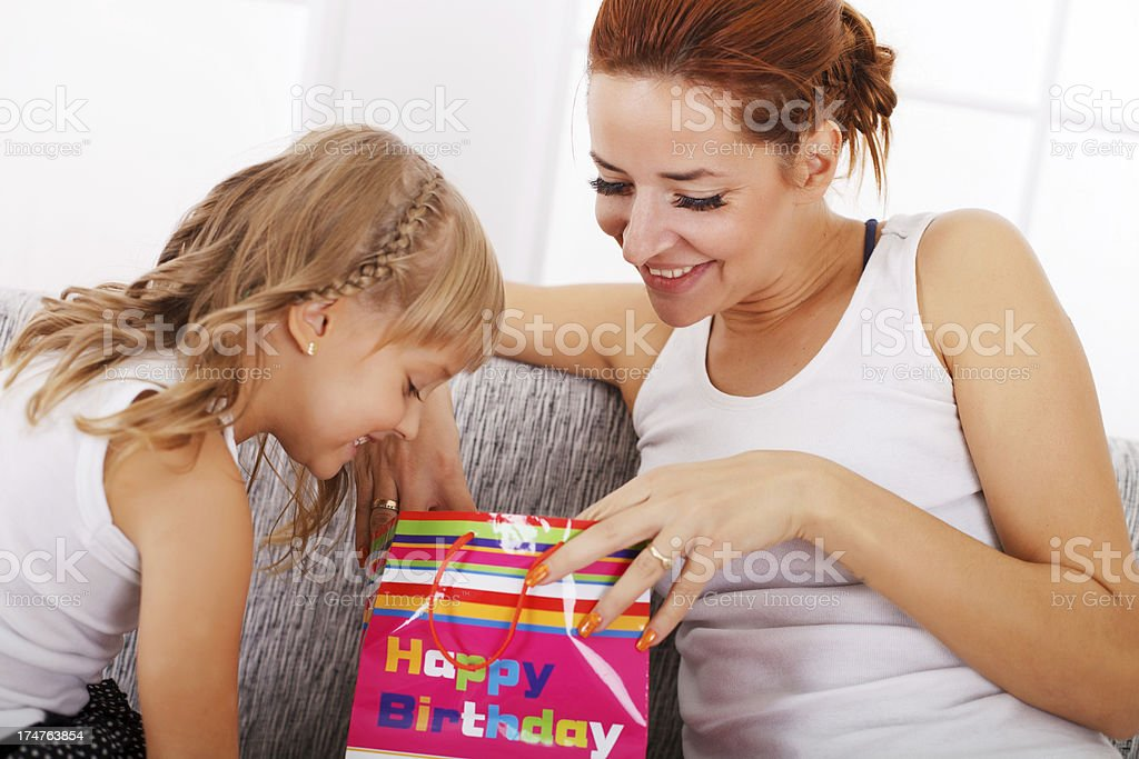 Mother And Daughter Looking At Birthday Gift Royalty Free Stock Photo