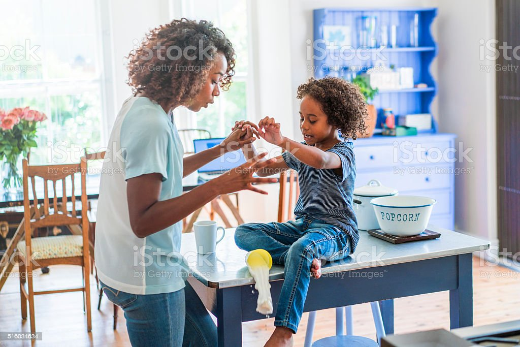 Mother and daughter looking at food spilling from glass stock photo