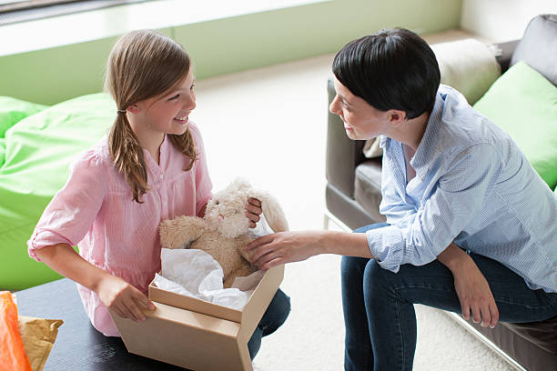 mother and daughter looking at stuffed animal - happy mom packing some toys stock photos and pictures