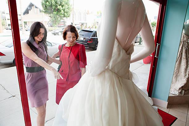 mutter und tochter, die ein hochzeitskleid im shop fenster - hochzeitskleid über 50 stock-fotos und bilder