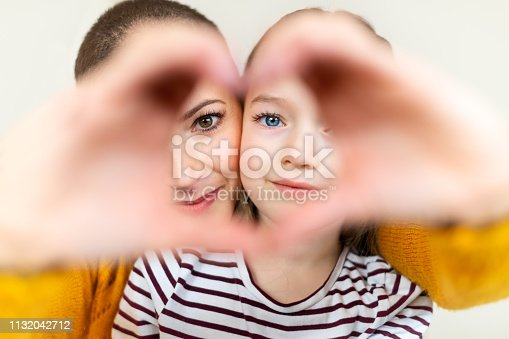 516544386 istock photo Mother and daughter looking through heart shaped love symbol hand gesture. Family, love, togetherness concept. 1132042712