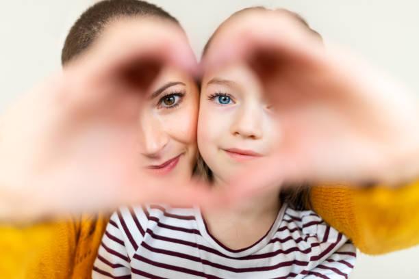 Mutter und Tochter, die durch das Herz schauten, prägten Liebessymbol Handbewegung. Familie, Liebe, Zusammengehörigkeit Konzept. – Foto