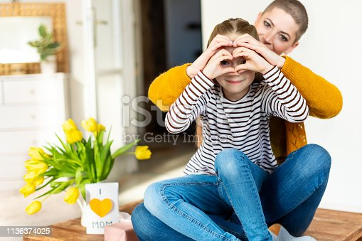 istock Mother and daughter looking through heart shaped love symbol hand gesture. Family, love, togetherness concept. 1136374025