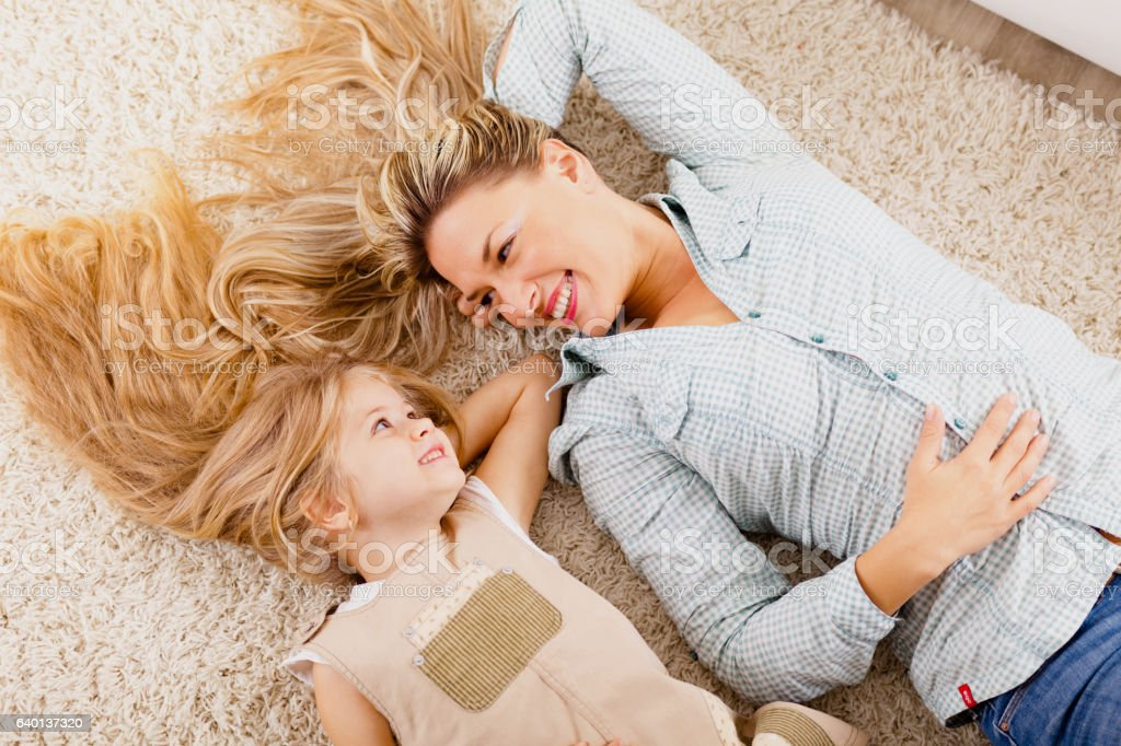 Mother and daughter lying on carpet and relaxing stock photo