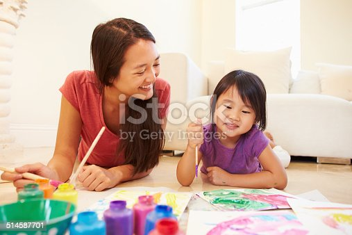 Mother And Daughter Lying On Floor And Painting Picture Smiling