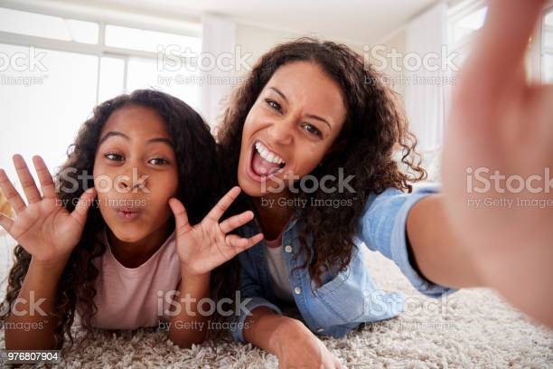 Mother and daughter lying on rug and posing for selfie at home picture id976807904?b=1&k=6&m=976807904&s=612x612&h=yzbmagaajx8i09dtic6f1fn8pmgkdgpdj17nv qbqiw=