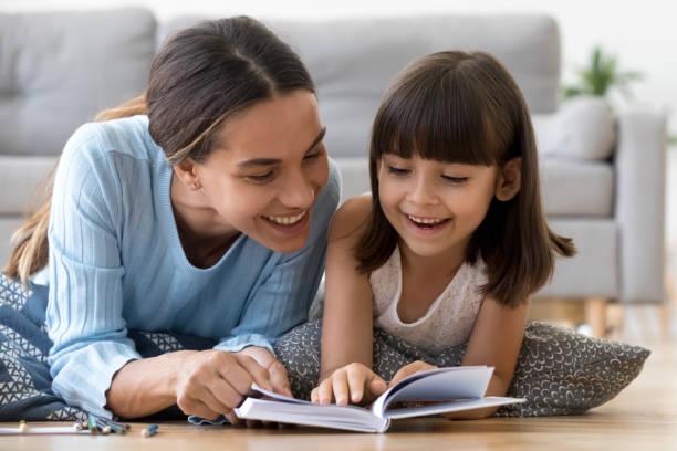 madre e hija en cálido suelo leer libro - niñera fotografías e imágenes de stock