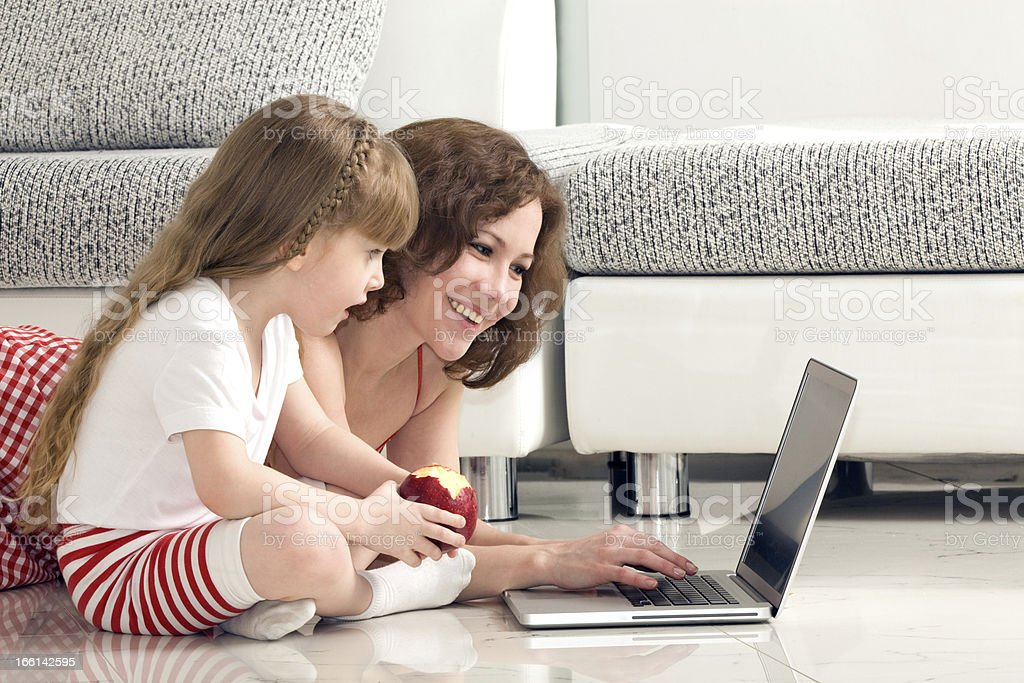 Mother and Daughter Lying with the Laptop. stock photo