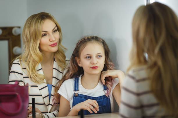 Mutter und Tochter machen Make-up zusammen. Reflexion im Spiegel – Foto