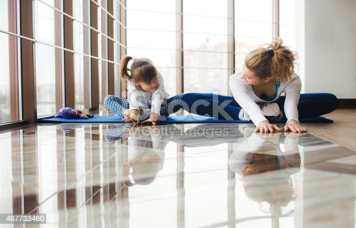 istock Mother and daughter makeing yoga in the gym 467733460