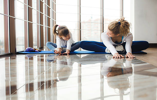Mother and daughter makeing yoga in the gym stock photo