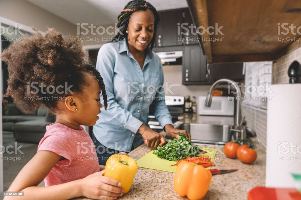 mother and daughter making a salad stock photo