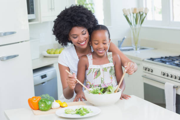 Mother and daughter making a salad together stock photo