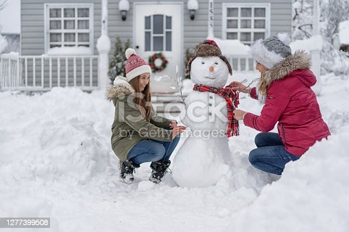 Mother and daughter making a snowman in front of the house. Shot taken from the street at the end of the driveway across piled snowdrifts and deep snow on the front yard.