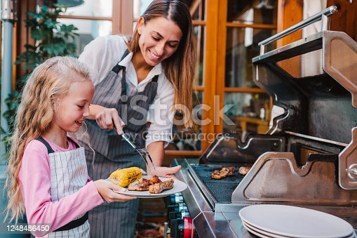 Young happy woman and cute cheerful girl grilling meat and corn on a barbecue grill in the backyard of their house.