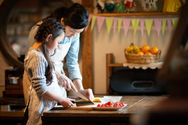 Mother and daughter making cake at home stock photo