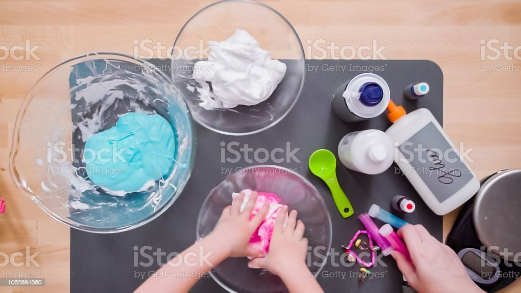 Mother and daughter making colorful fluffy slime. Step by step. Flat lay. Mother and daughter making colorful fluffy slime. Above Stock Photo