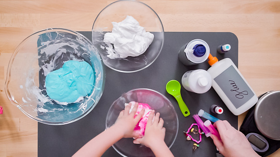 Mother And Daughter Making Colorful Fluffy Slime Stock Photo - Download Image Now