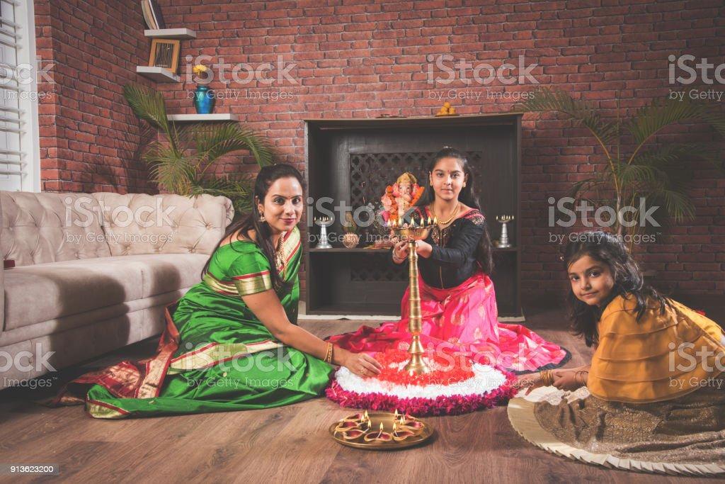 Mother and daughter making flower rangoli and girl lighting diya or samai stock photo
