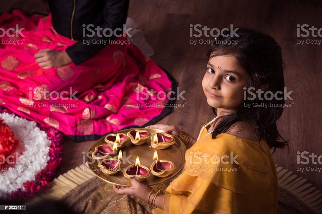 Mãe e filha fazendo rangoli flor e garota iluminação diya ou samai - foto de acervo