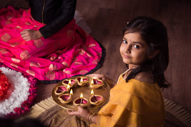 mother and daughter making flower rangoli and girl lighting diya or samai - diwali stock pictures, royalty-free photos & images