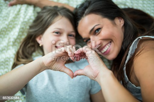 istock Mother and daughter making heart shape from hand while lying on bed 652632584