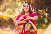 Mother and daughter showing love by making heart shape with hands at Long bay park, Auckland, New Zealand.
