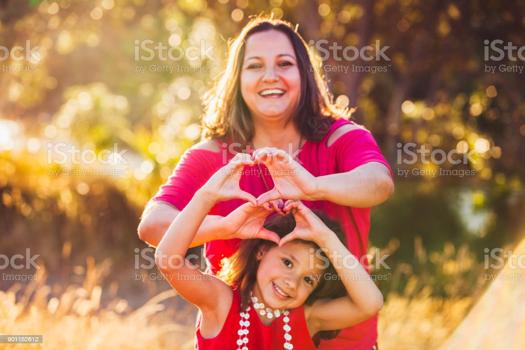 Mother and daughter making heart shape. stock photo