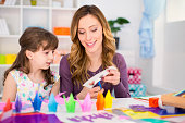 Cheerful mother and daughter making origami. Can be also used for education/kindergarten concept.