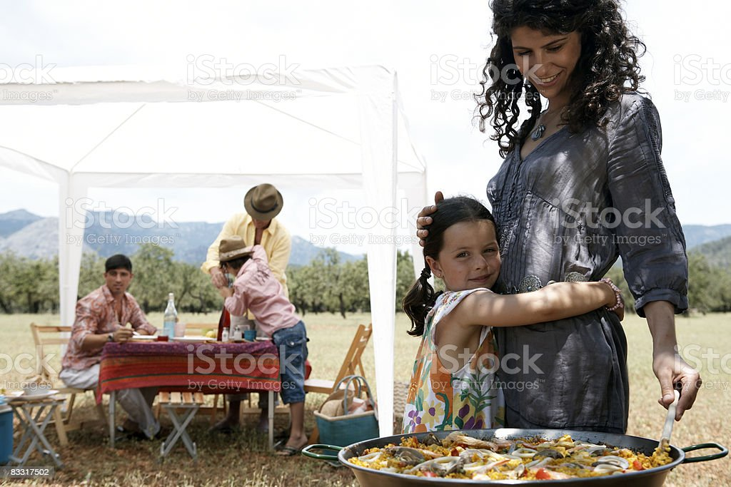 mother and daughter making paella outdoors royalty free stockfoto