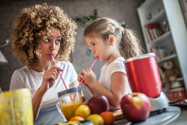 Mother and daughter making  smoothie Mother and daughter making  smoothie blender stock pictures, royalty-free photos & images
