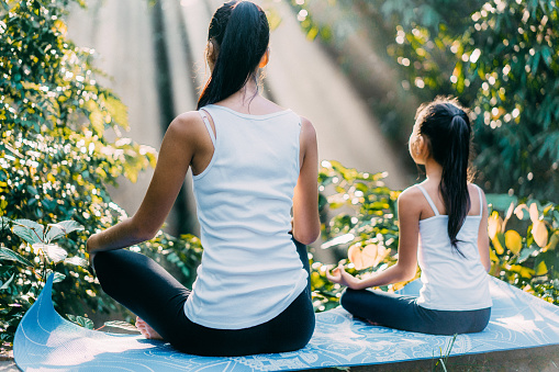 Asian mother  and daughter meditating in lotus position in rainforest in Bali, Indonesia