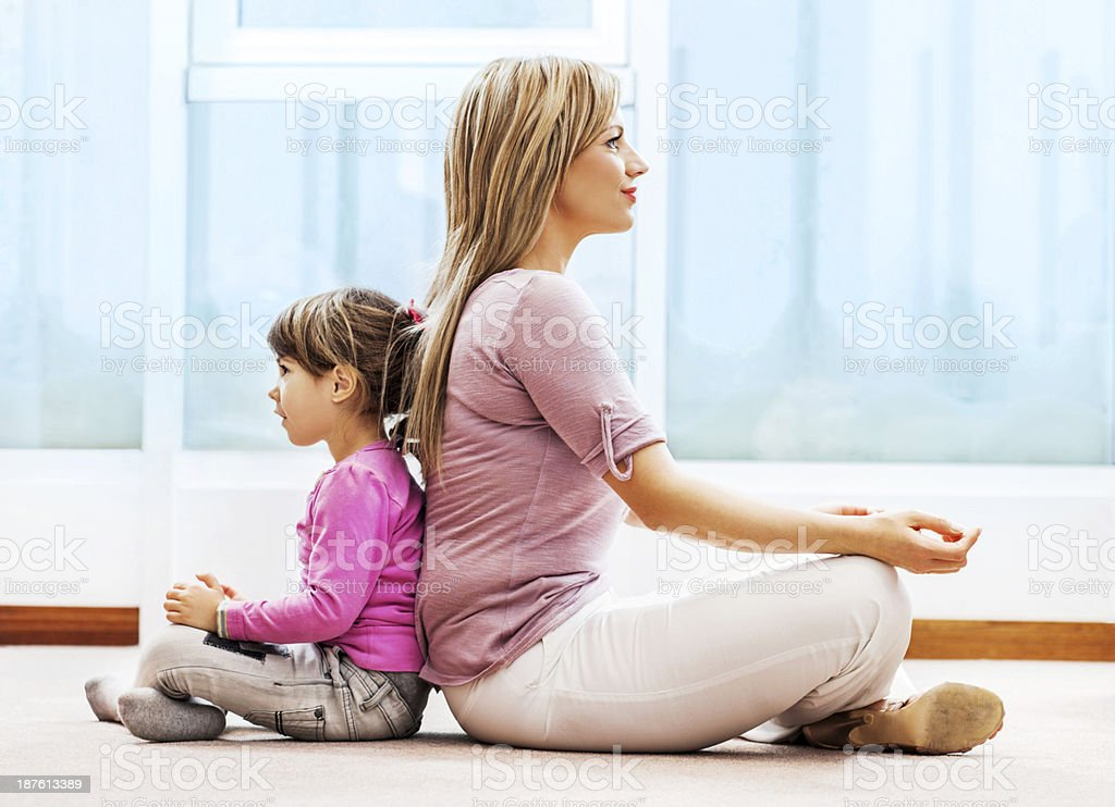 Mother and daughter meditating. royalty-free stock photo
