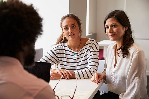 Mother And Daughter Meeting With Male Teacher stock photo